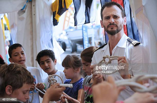 A French National Marine sailor shows children how to tie a sailor's knot during a demonstration at the 'Escales Marines' event dedicated to the...