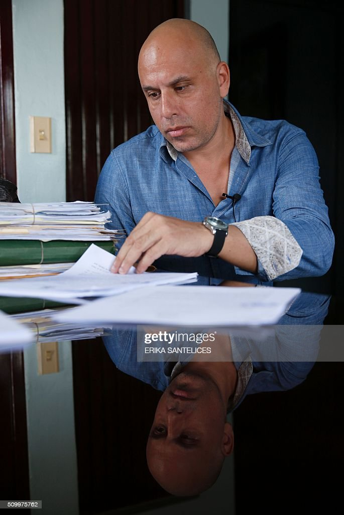 French national Nicolas Pisapia, accused of trying to fly dozens of suitcases packed with cocaine from the Dominican Republic to France, checks documents during an interview in the office of his Dominican lawyer Andy De Leon in Higuey, Altagracia province, Dominican Republic on February 13, 2016. Pisapia was arrested with French nationals Alain Castany, pilot Pascal Fauret and co-pilot Bruno Odos in March 2013 as they were about to take off from the Dominican resort of Punta Cana in a case dubbed 'Air Cocaine' in France. AFP PHOTO / ERIKA SANTELICES / AFP / ERIKA SANTELICES