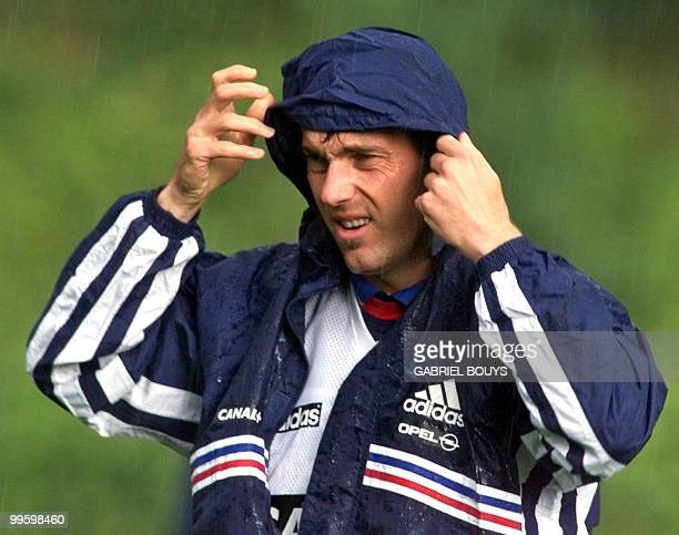 French national soccer team defender Laurent Blanc covers his head during a rainy training session 14 June in Clairefontaine outside Paris where...