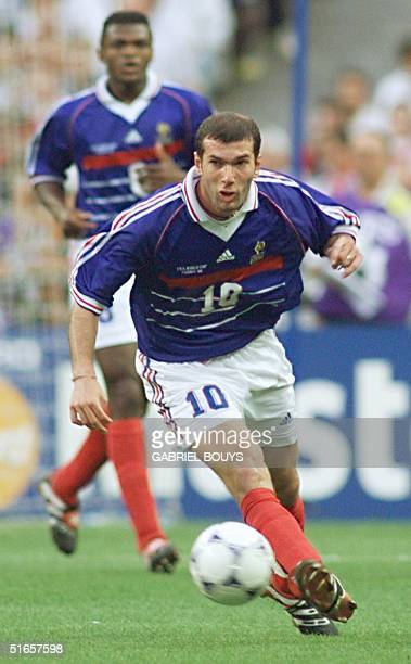 French national soccer team Zinedine Zidane kicks the ball as teammate Marcel Desailly looks on 12 July during the 1998 Soccer World Cup final match...