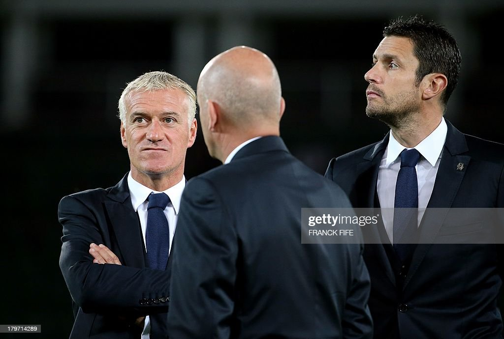 French national soccer team's coach Didier Deschamps (L) looks at his players warming up prior to the FIFA World Cup 2014 qualifying football match Georgia vs France on September 6 2013 at the Boris Paichadze stadium in Tbilisi.