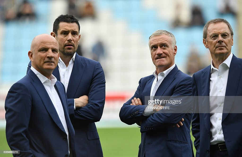French national team staff, Assistant coach Guy Stephan, fitness coach Eric Bedouet, head coach Didier Deschamps and goalkeeper coach Franck Raviot look on prior to the friendly football match between France and Cameroon, at the Beaujoire Stadium in Nantes, western France, on May 30, 2016. / AFP / FRANCK