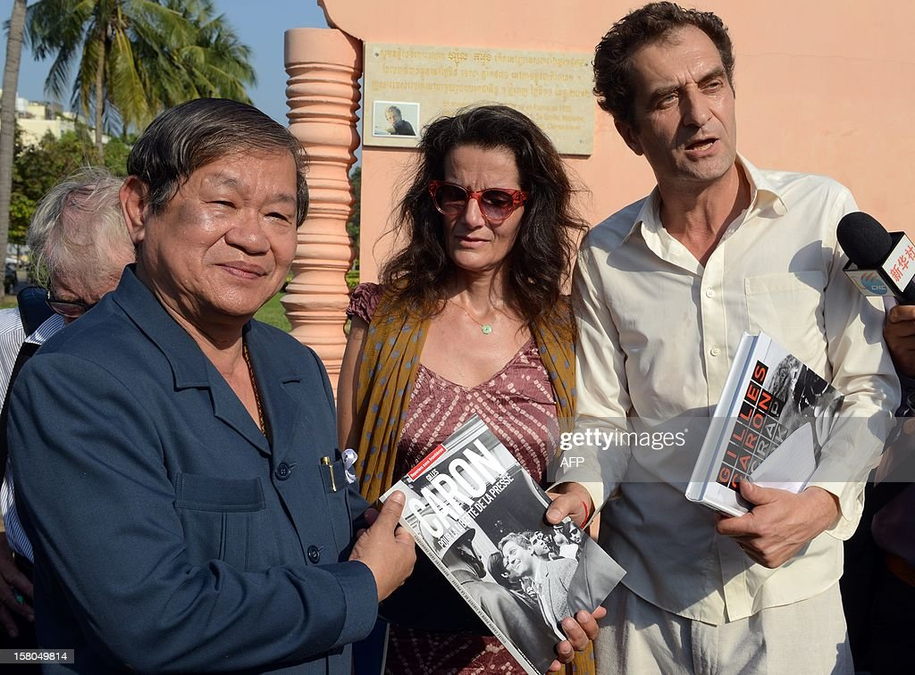 French nationals Louis Bachelot (R), president of Gilles Caron foundation and Marjolaine Caron (C), daughter of former French journalist Gilles Caron hand over a book about Gilles Caron to Cambodian minister of information and government spokesman Khieu Kanharith (L) at a memorial sign at park in front of the Le Royal hotel in Phnom Penh on December 10, 2012. Gilles Caron was one amongst 37 foreign and local journalists who died covering Cambodia's 1970-1975 war. AFP PHOTO/TANG CHHIN SOTHY