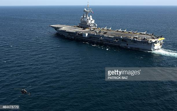 A French navy Allouette III rescue helicopter flies by the aircraft carrier Charles de Gaulle as fighter jets prepare to take off from the ship for a...