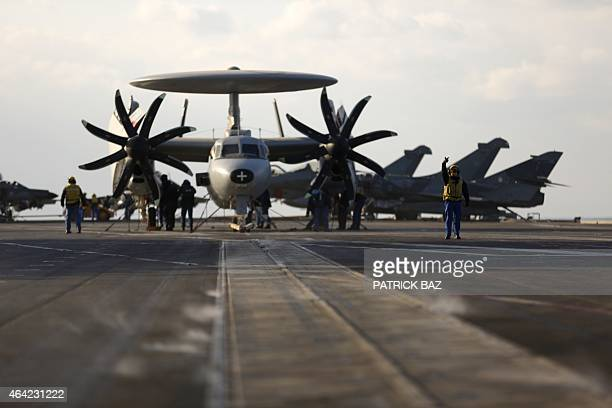 A French Navy HawkEye reconnaissance plane sit on the deck of the French Navy aircraft carrier Charles de Gaulle operating in the Gulf on February 23...