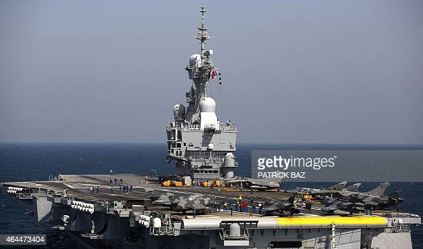 French navy Rafale fighter jets and Super Etendard sit on the deck of the aircaft carrier Charles de Gaulle operating in the Gulf on February 26 2015...