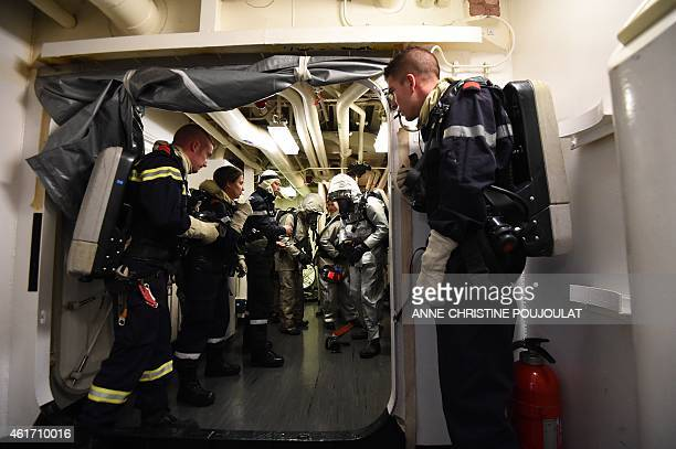 French navy soldiers fight a mock fire during a security exercise aboard the aircraft carrier Charles de Gaulle at sea off the coast of Toulon...