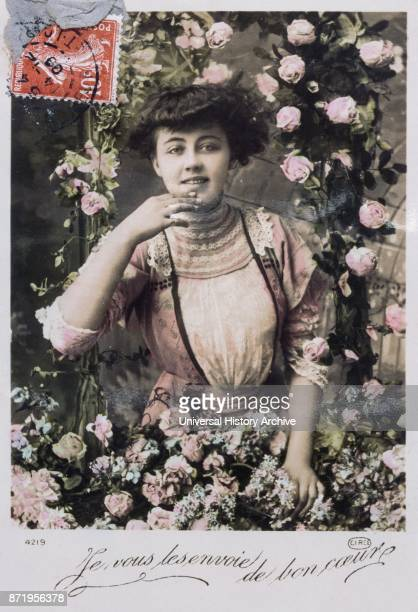 French new year postcard depicting a middle class woman smiling and surrounded by flowers 1900