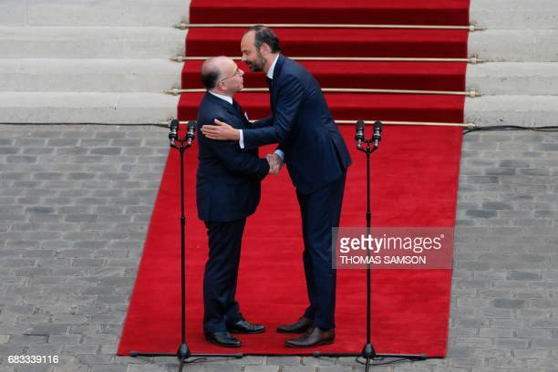 French newly appointed Prime Minister Edouard Philippe embraces his predecessor Bernard Cazeneuve as they shake hands at the end of an official...