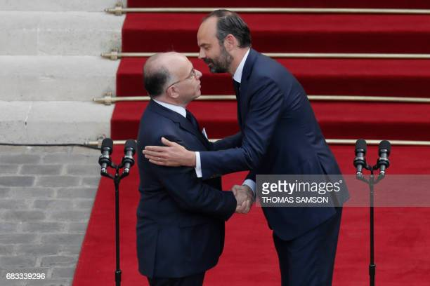TOPSHOT French newly appointed Prime Minister Edouard Philippe embraces his predecessor Bernard Cazeneuve as they shake hands at the end of an...