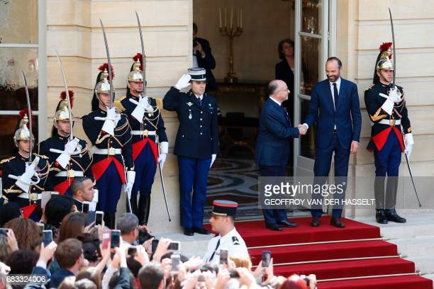 French newly appointed Prime Minister Edouard Philippe is welcomed by his predecessor Bernard Cazeneuve as they shake hands at the Hotel Matignon in...