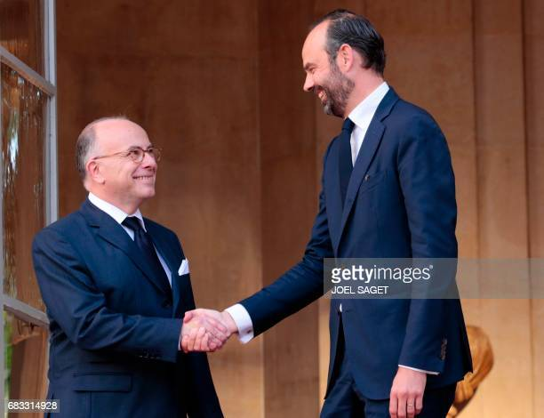 TOPSHOT French newly appointed Prime Minister Edouard Philippe smiles as he is welcomed by his predecessor Bernard Cazeneuve at the Hotel Matignon in...