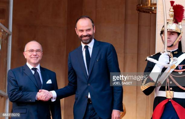 French newly appointed Prime Minister Edouard Philippe smiles as he is welcomed by his predecessor Bernard Cazeneuve at the Hotel Matignon in Paris...