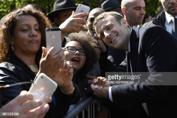 TOPSHOT French newly elected president Emmanuel Macron poses for pictures with supporters on May 10 2017 at the Jardins du Luxembourg in Paris during...