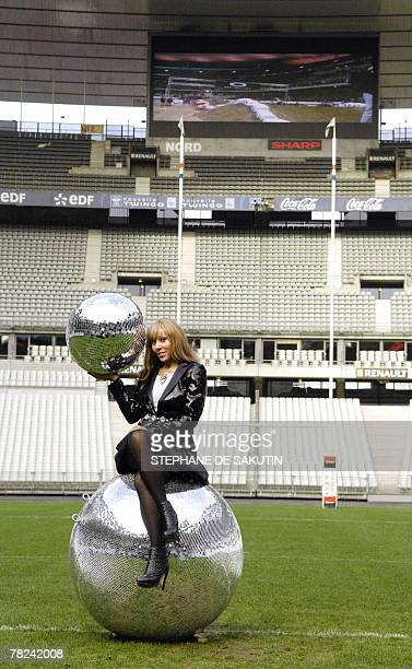 French nightclub owner Cathy Guetta sits on a giant mirror ball 04 December 2007 in SaintDenis near Paris at the Stade de France where she will...