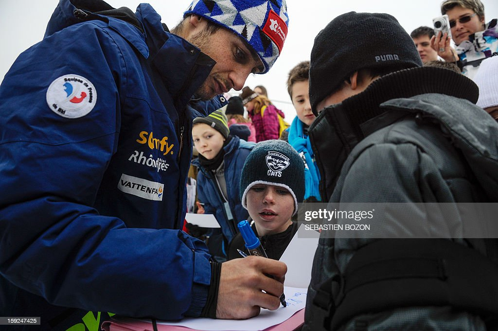 French Nordic Combined champion Jason Lamy-Chappuis (L) signs autographs to children after a training session on January 10, 2013 at the international ski jumping facility of Chaux-Neuve, eastern France. AFP PHOTO / SEBASTIEN BOZON