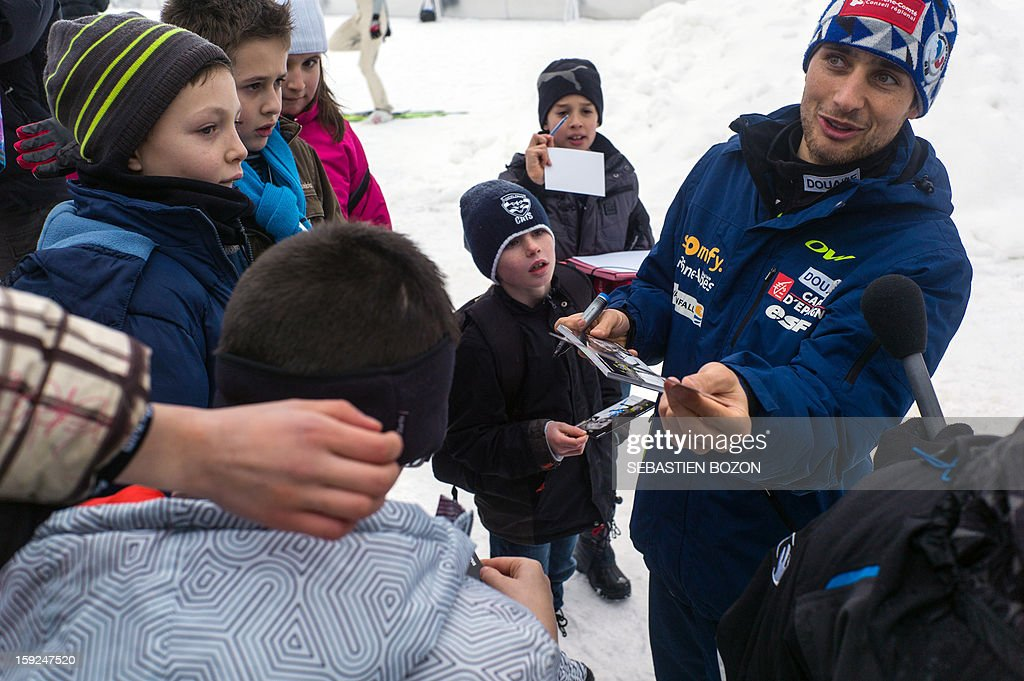 French Nordic Combined champion Jason Lamy-Chappuis (R) signs autographs to children after a training session on January 10, 2013 at the international ski jumping facility of Chaux-Neuve, eastern France. AFP PHOTO / SEBASTIEN BOZON