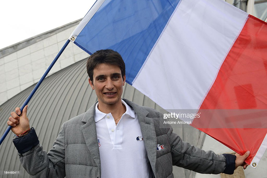 French nordic combined ski champion Jason Lamy Chappuis poses with his national flag after being chosen as his countries flag bearer for the Sochi 2014 Winter Olympics on October 14, 2013 in Paris, France.