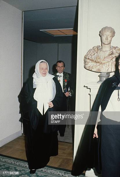 French novelist Marguerite Yourcenar enters 'the Room of 40' with French academician Jean d'Ormesson in the French Academy building in Paris on...