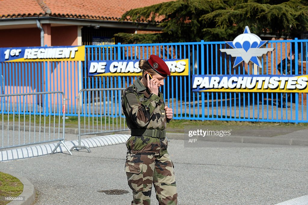 French officer Florence Clapie speaks on phone to a journalist on March 3, 2013 in Pamiers, southwestern France, in front of the entrance of the 1st Parachute Chasseur Regiment barracks (RCP), an airbone infantry unit of the French Army, where the French soldier killed in northern Mali on March 2 was based. France said on March 3 that one of its soldiers had been killed in fighting in northern Mali, in the third death of a French serviceman since the launch of its military intervention in mid-January. The defence ministry identified the soldier as Corporal Cedric Charenton, 26, who had been deployed in Mali since January 25 and had previously served in Afghanistan and Gabon.