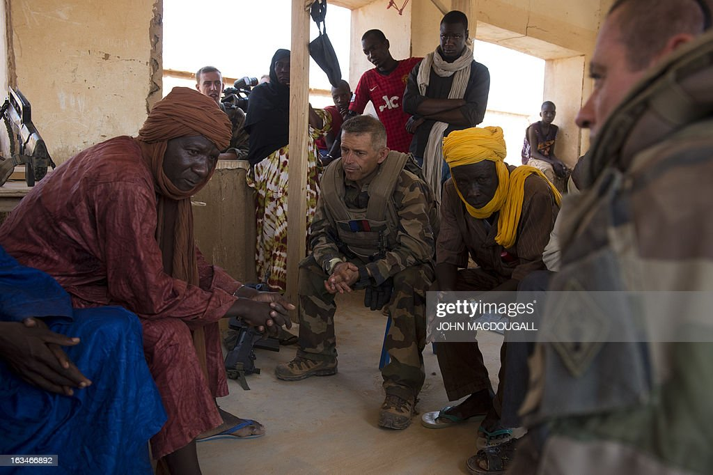 A French officer (C) speaks to village elders to assess the situation, in the village of Amakouladji, north of Gao, on March 10, 2013.