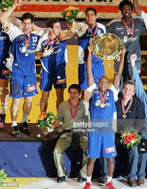 French Olivier Girault held up the trophy as his teammates and coach Claude Onesta celebrate during the European handball championships final between...
