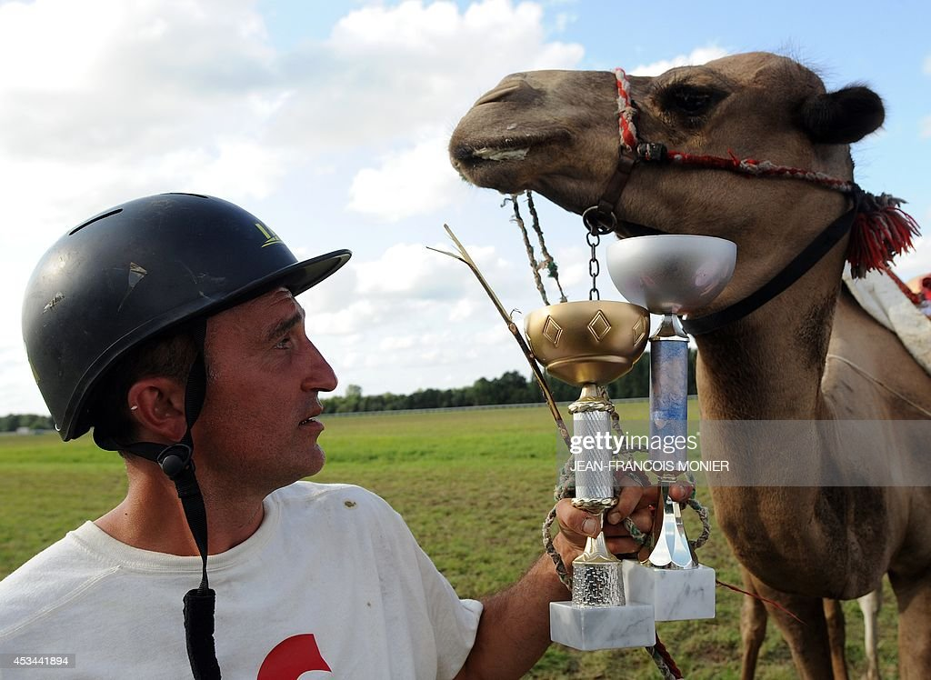 French Olivier Philipponneau poses with the trophy after winning during a French Cup of camel races on August 10, 2014 on the horserace track of La Chartre-sur-le-Loir, western France. Unusual in these latitudes, eight dromaderies that have never seen the desert, took part in two races of 1000 meters.
