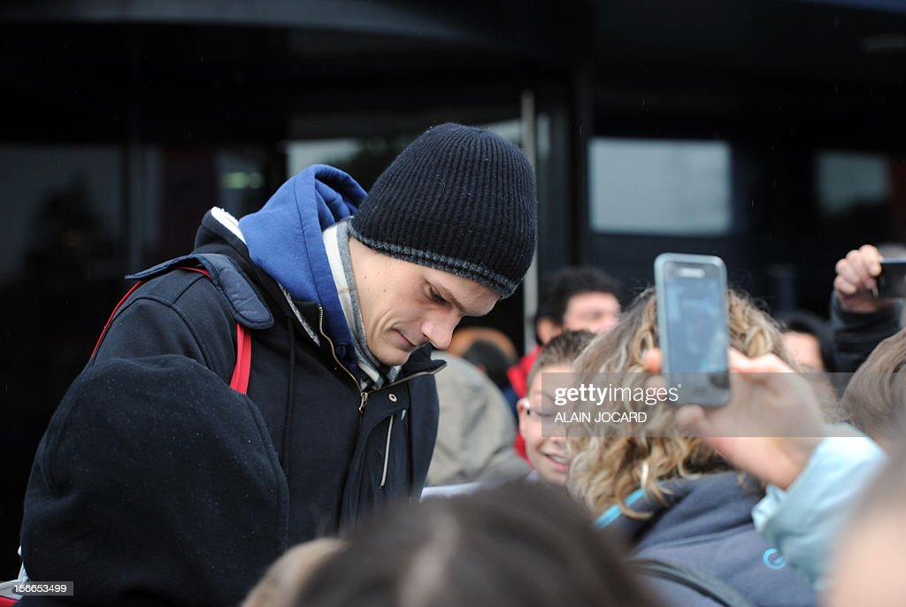 French Olympic 200m freestyle and 4x100m relay champion Yannick Agnel (L) signs autographs at the French championships, on November 18, 2012, in Angers, western France.