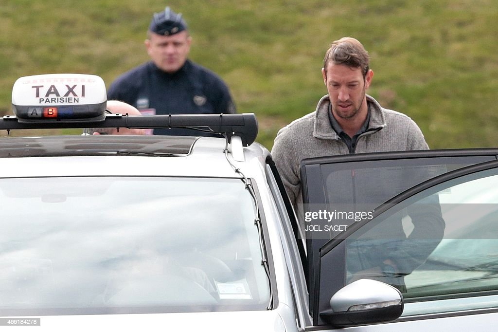 French Olympic champion swimmer <a gi-track='captionPersonalityLinkClicked' href=/galleries/search?phrase=Alain+Bernard+-+Swimmer&family=editorial&specificpeople=775873 ng-click='$event.stopPropagation()'>Alain Bernard</a> enters a taxi outside the Honours Pavilion at Paris Roissy-Charles-de-Gaulle airport, after the arrival from Argentina of French sports stars and crew from the reality TV series 'Dropped', on March 14, 2015. French sports stars and crew from the ill-fated reality TV series 'Dropped' landed in France on March 14, as experts investigate this week's helicopter crash that killed 10 people, including three top French athletes. AFP PHOTO / JOEL SAGET