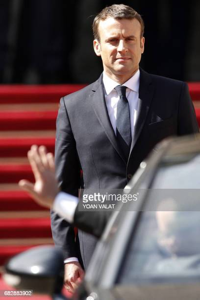 French outgoing President Francois Hollande waves from his car as he leaves the Elysee presidential Palace at the end of the handover ceremony and...