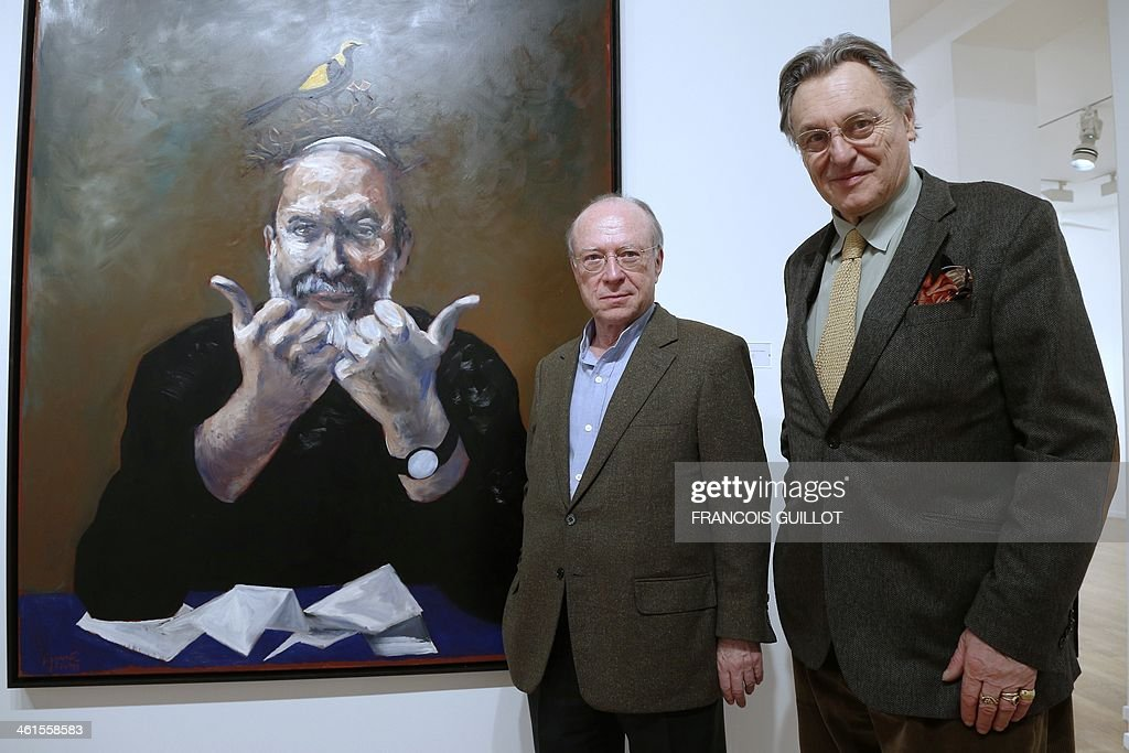 French painter Gerard Garouste (R) and French contemporary and modern art dealer Daniel Templon (L) pose in front of one of Garouste's works, on January 9, 2014 in Paris, prior to a new exhibition organized at the Templon Galerie from January 11 to February 26. AFP PHOTO FRANCOIS GUILLOT CAPTION