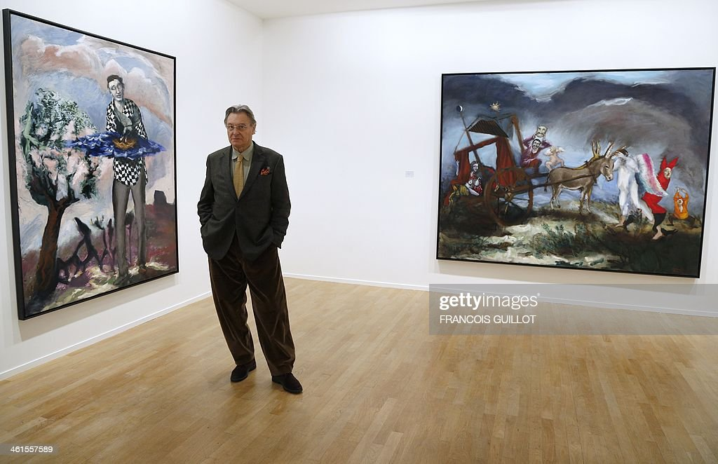 French painter Gerard Garouste poses in front of two of his works, on January 9, 2014 in Paris, prior to a new exhibition organized at the Templon Galerie from January 11 to February 26. AFP PHOTO FRANCOIS GUILLOT CAPTION