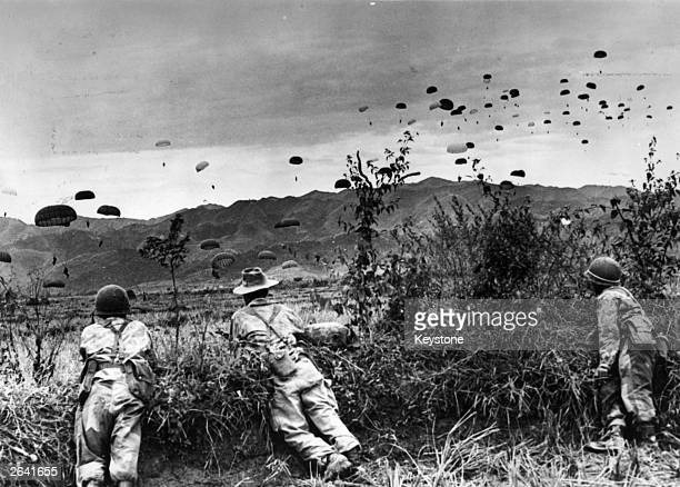 French parachutists watching comrades being dropped over Dien Bien Phu an enemy stronghold which was captured by the paratroopers during the Indo...