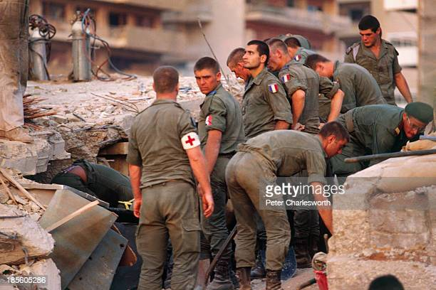 French paratroopers serach through the rubble all that remained of the eightstory 'Drakkar' building which had been used as the French military's...