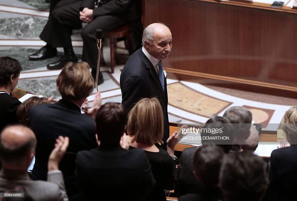 French Parliament members applauds outgoing French Foreign Minister Laurent Fabius (C) during the questions to the government at the National Assembly in Paris on February 10, 2016. French lawmakers were to vote on February 10 on a controversial package of measures to change the constitution following the terror attacks on Paris in November. / AFP / JACQUES DEMARTHON