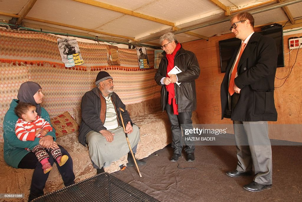 French Patrick Le Hyaric (2nd R), a member of the European Parliament, talks to a Palestinian man during a visit by a delegation of European MPs to the Palestinian village of Susya, south-east of Hebron, in the Israeli-occupied West Bank, on February 10, 2016. Israel's High Court ruled in May 2015 that Susya's 340 residents could be relocated and its structures demolished, which Human Rights Watch derided as 'a grave breach' of Israel's obligations to the Palestinian populace under its military rule. / AFP / HAZEM BADER