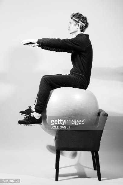 French performance artist Abraham Poincheval poses on an exercise ball placed on a chair during a photo session in Paris on February 20 2017...