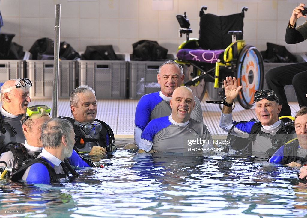 French Philippe Croizon (C), 44, celebrates on January 10, 2013 with a group of 15 Belgian divers after becoming the first quadruple amputee to dive at a depth of 33 meters in the deepest swiming pool in the world in Brussels. He used flippers attached to prosthetic limbs to dive to the bottom of the pool to set a new world record for an amputee. Croizon had all four limbs amputated in 1994 after being struck by an electric shock of more than 20,000 volts as he tried to remove a TV antenna from a roof. He has swum across the English Channel and all five intercontinental channels.