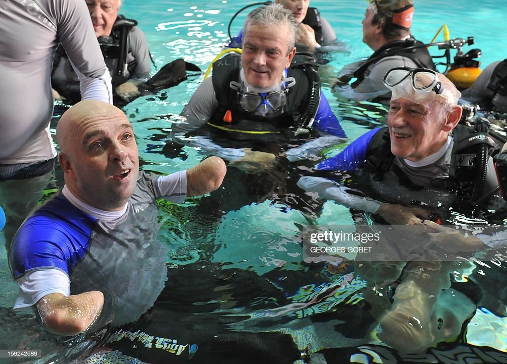 French Philippe Croizon (L), 44, celebrates on January 10, 2013with a group of 15 Belgian divers after becoming the first quadruple amputee to dive at a depth of 33 meters in the deepest swiming pool in the world in Brussels. He used flippers attached to prosthetic limbs to dive to the bottom of the pool to set a new world record for an amputee. Croizon had all four limbs amputated in 1994 after being struck by an electric shock of more than 20,000 volts as he tried to remove a TV antenna from a roof. He has swum across the English Channel and all five intercontinental channels.