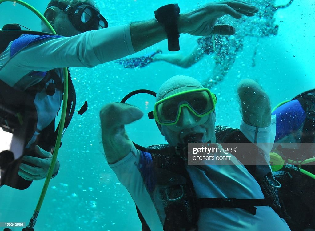 French Philippe Croizon, 44, celebrates underwater on January 10, 2013 after becoming the first quadruple amputee to dive at a depth of 33 meters in the deepest swiming pool in the world in Brussels. He used flippers attached to prosthetic limbs to dive with a group of 15 Belgian divers to the bottom of the pool to set a new world record for an amputee. Croizon had all four limbs amputated in 1994 after being struck by an electric shock of more than 20,000 volts as he tried to remove a TV antenna from a roof. He has swum across the English Channel and all five intercontinental channels.