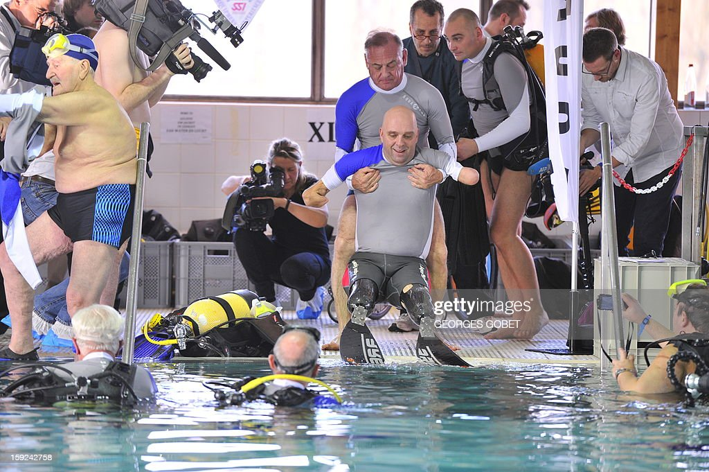 French Philippe Croizon (C), 44, is lifted out of the pool on January 10, 2013 after becoming the first quadruple amputee to dive at a depth of 33 meters in the deepest swiming pool in the world in Brussels. He used flippers attached to prosthetic limbs to dive to the bottom of the pool to set a new world record for an amputee. Croizon had all four limbs amputated in 1994 after being struck by an electric shock of more than 20,000 volts as he tried to remove a TV antenna from a roof. He has swum across the English Channel and all five intercontinental channels.