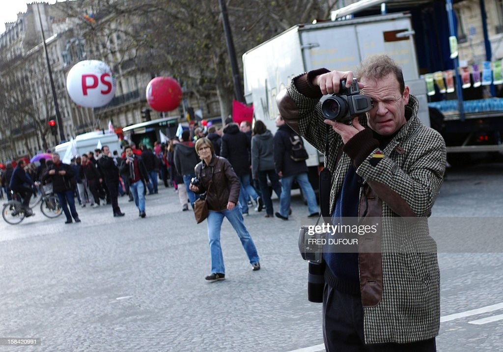 French photographer Francois-Marie Banier takes photos during a demonstration for the legalisation of gay marriage and LGBT (lesbian, gay, bisexual, and transgender) parenting in Paris on December 16, 2012.