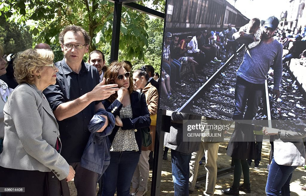 French photographer Olivier Jobard (2L) presents his photos to Mayor of Madrid, Manuela Carmena (L) during the opening of the exhibition 'Caminos de Exilio' ('Ways of Exile') at Retiro Park in Madrid, on 31 May 2016. The exhibition shows pictures of refugees taken by five photographers; Sima Diab (Syria), Giorgios Moutafis (Greece), Manu Brabo (Spain), Olivier Jobard (France) and Pierre Marsaut (France) and has been organized by the French Embassy and the French Institute in Spain, on the sidelines photo festival of PhotoEspana 2016. / AFP / GERARD