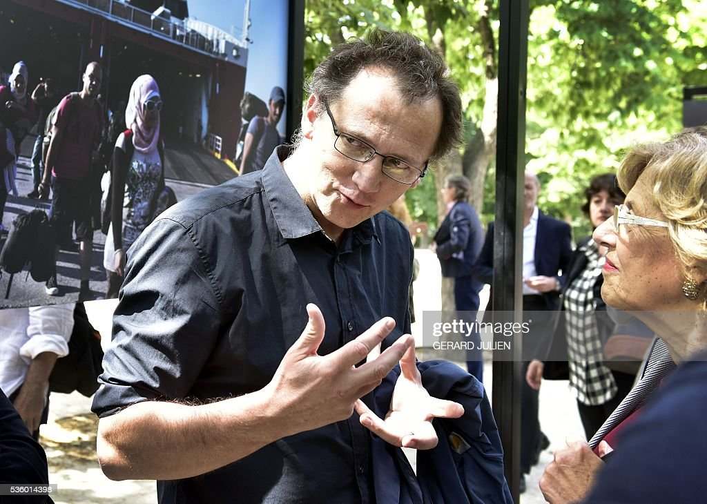 French photographer Olivier Jobard speaks with Mayor of Madrid, Manuela Carmena (R) during the opening of the exhibition 'Caminos de Exilio' ('Ways of Exile') at Retiro Park in Madrid, on 31 May 2016. The exhibition shows pictures of refugees taken by five photographers; Sima Diab (Syria), Giorgios Moutafis (Greece), Manu Brabo (Spain), Olivier Jobard (France) and Pierre Marsaut (France) and has been organized by the French Embassy and the French Institute in Spain, on the sidelines photo festival of PhotoEspana 2016. / AFP / GERARD