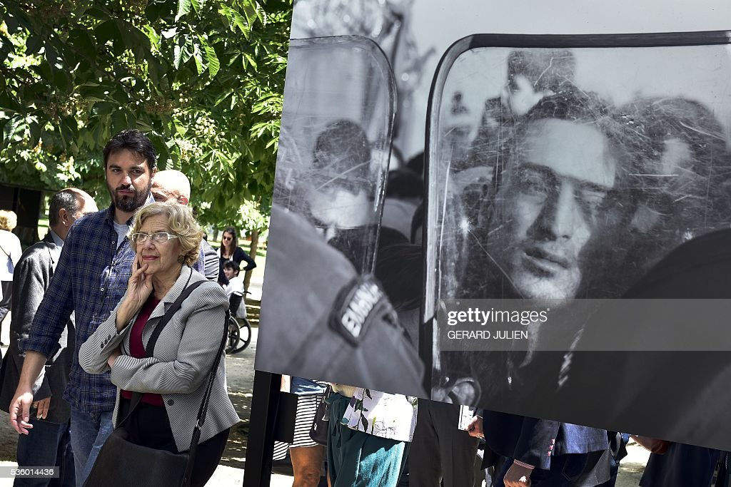 French photographer Pierre Marsaut (L) presents his photos to Mayor of Madrid, Manuela Carmena (2L) during the opening of the exhibition 'Caminos de Exilio' ('Ways of Exile') at Retiro Park in Madrid, on 31 May 2016. The exhibition shows pictures of refugees taken by five photographers; Sima Diab (Syria), Giorgios Moutafis (Greece), Manu Brabo (Spain), Olivier Jobard (France) and Pierre Marsaut (France) and has been organized by the French Embassy and the French Institute in Spain, on the sidelines photo festival of PhotoEspana 2016. / AFP / GERARD