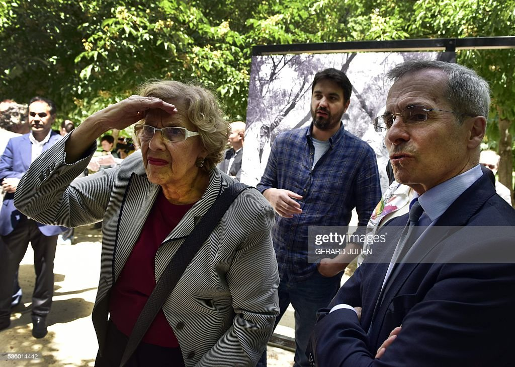 French photographer Pierre Marsaut (C) presents his photos to Mayor of Madrid, Manuela Carmena (L) and French Ambassador in Spain, Yves Saint-Geours (R) during the opening of the exhibition 'Caminos de Exilio' ('Ways of Exile') at Retiro Park in Madrid, on 31 May 2016. The exhibition shows pictures of refugees taken by five photographers; Sima Diab (Syria), Giorgios Moutafis (Greece), Manu Brabo (Spain), Olivier Jobard (France) and Pierre Marsaut (France) and has been organized by the French Embassy and the French Institute in Spain, on the sidelines photo festival of PhotoEspana 2016. / AFP / GERARD