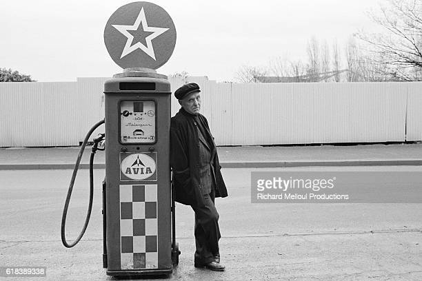 French photographer Robert Doisneau leans against a fuel pump in Paris