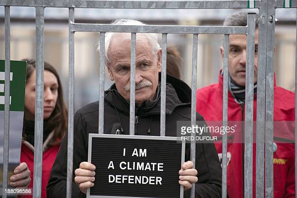 French photographer Yann Arthus Bertrand poses as he stands in a cage with Greenpeace activists on November 15 2013 in Paris This demo is held as 30...