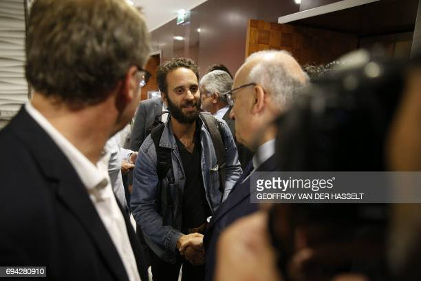 French photojournalist Mathias Depardon shakes hands with French president's diplomatic advisor Philippe Etienne after Depardon landed from Istanbul...