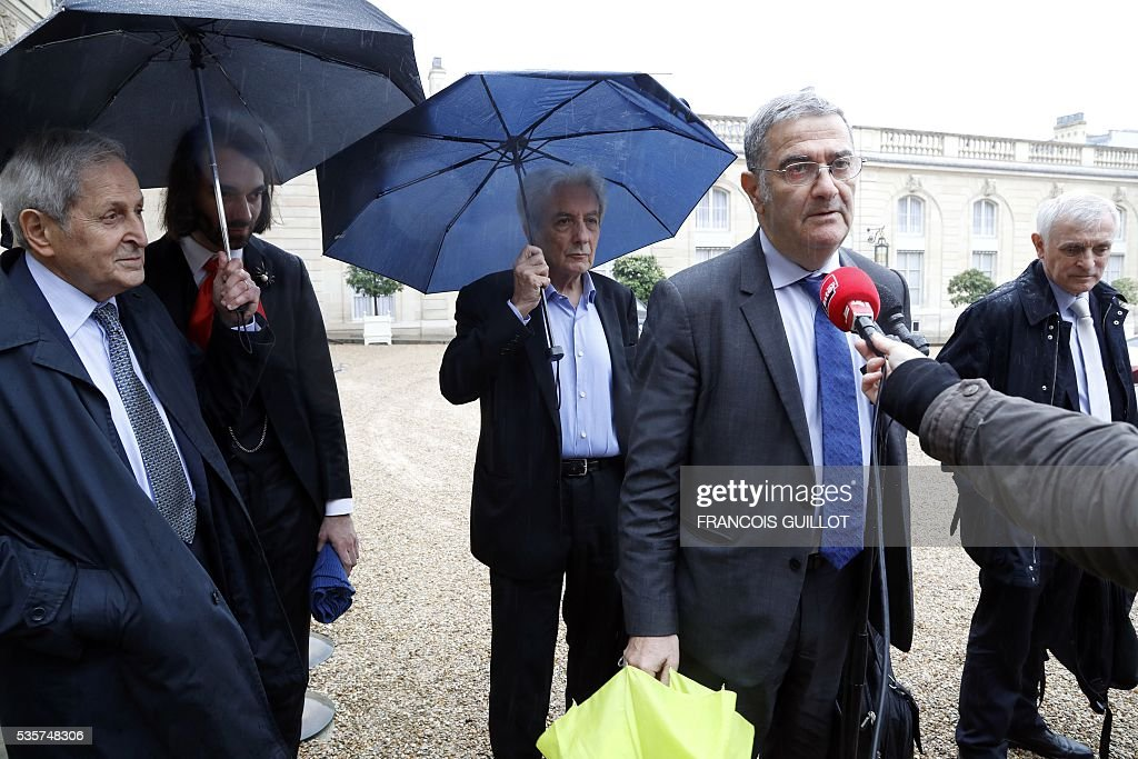 French physicist Serge Haroche (2nd R) speaks to the press next to French physicist Claude Cohen-Tannoudji (L), French mathematician Cedric Villani (2nd L), French physicists Albert Fert (C) and French climatologist and glaciologist Jean Jouzel as they leave the Elysee palace in Paris following a meeting with the French President on May 30, 2016 following an article, signed by seven Nobel Prize winners and one Fields medal winner, published in the French newspaper Le Monde regarding the draft decree of budget cuts in research and higher education. French President Francois Hollande has removed credit cuts of 134 millions of euros from the budget of the research, said Nobel Prize winner Serge Haroche after having been received at the Elysee Palace with five other leading scientists.